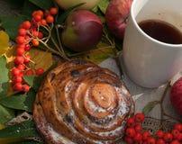 Eine Schale starker schwarzer Tee, süßes Brötchen mit Rosinen, Aschbeeren, Äpfel und bunter Herbstlaub auf einer Steinoberfläche Stockbilder