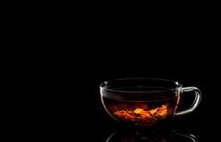 Eine Schale wohlriechender heißer Tee auf einem schwarzen Hintergrund Lizenzfreies Stockfoto