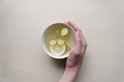 Eine Schale Zitronensäfte mit Zitrone bessert in der Hand aus Lizenzfreie Stockbilder