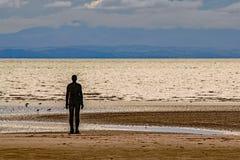 Eine Schattenbildzahl, die den Horizont an Crosby-Strand, England gegenüberstellt lizenzfreie stockfotos