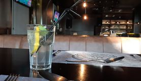 Eine Scheibe der Orange in einem Glas mit funkelndem Wasser Ein Glas Wasser mit einer Scheibe der Zitrone, stockfotografie