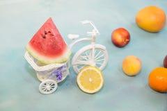 Eine Scheibe der Wassermelone auf einem dekorativen Fahrrad mit der Frucht geholt auf einen blauen Hintergrund stockbilder