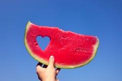 Eine Scheibe der Wassermelone und des Herzens gegen den hellen Sommerhimmel in der Mädchen ` s Hand stockfotos