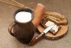 Eine Scheibe des gebutterten Brotes auf einem hölzernen Brett, einem Topf Milch und reifen Ohren Stockfotos