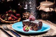 Eine Scheibe des Schokoladenkuchens mit Erdbeeren auf einer blauen Platte Sugar Snow stockbilder