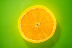 Eine Scheibe orange Nahaufnahme auf grünem Hintergrund, horizontaler Schuss Stockfotografie