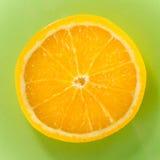 Eine Scheibe orange Nahaufnahme auf grünem Hintergrund, quadratischer Schuss Stockfotografie