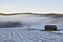 Eine Scheune auf einer schneebedeckten Wiese mit blauem Himmel und Nebel im Hintergrund Lizenzfreie Stockfotografie