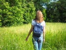 Eine schlanke Frau mit einem Rucksack reist auf das hohe Gras lizenzfreie stockfotos