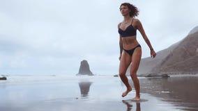 Eine schlanke Frau nahe dem Ozean gehend auf den Wassersport zur Ausführung von Laufleinen auf jedem Bein Übungen für Schenkelmus stock video