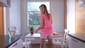 Eine schlanke glückliche Frau in den Pyjamas, die ein gesundes Frühstück und ein Tanzen vorbereiten stock footage