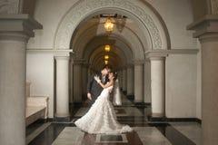 Eine schöne Braut und ein hübscher Bräutigam an der christlichen Kirche während der Hochzeit. Lizenzfreies Stockfoto