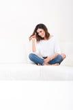 Eine schöne junge Frau auf der Couch Lizenzfreies Stockbild