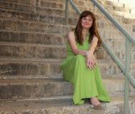 Eine schöne rote behaarte Frau, die auf Schritten sitzt Stockfotos