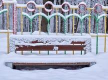 Eine schneebedeckte Holzbank- und Metallhecke hinten auf dem Winterhintergrund des Zauns stockfotografie