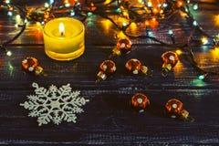 Eine Schneeflocke und eine Kerze auf einem Holztisch umgeben durch bunte Girlandenlichter Lizenzfreies Stockbild
