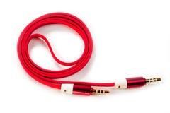 Eine Schnur mit 3 5mm helles rotes Verbindungsstück auf einem weißen Hintergrund Lizenzfreie Stockfotografie