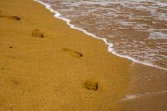 Eine Schnur von bloßen Abdrücken im Sand Wellen auf der Seeküste, sandiger Strand Schaum auf Meerwasser lizenzfreies stockfoto