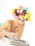 Eine Schreibensfrau in den Haar curles Lizenzfreie Stockfotos