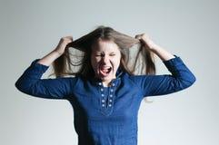 Eine schreiende Jugendliche, die auseinander ihr Haar über weißem Hintergrund oulling ist lizenzfreies stockfoto
