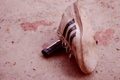 Eine Schuhe/Turnschuhe und ein Gewehr in der Straße mit Blutfleck im Hintergrund stockbild