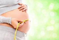 Eine schwangere Frau, die ihren Bauch mit einem Band misst Lizenzfreie Stockbilder