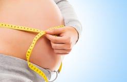 Eine schwangere Frau, die ihren Bauch mit einem Band misst Stockfotografie