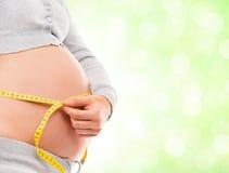 Eine schwangere Frau, die ihren Bauch mit einem Band misst Stockfoto
