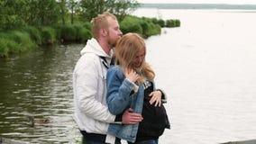 Eine schwangere Frau, die ihren Ehemann gegen den Hintergrund des Sees umarmt Junge Familie in Erwartung des Kinderwegs herein stock video