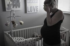 Eine schwangere Frau, die traurig und in einer Kindertagesstätte deprimiert schaut Lizenzfreie Stockbilder