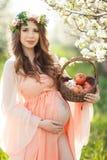 Eine schwangere Frau in einem Frühlingsgarten mit Korb Stockfotos