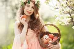 Eine schwangere Frau in einem Frühlingsgarten mit Korb Lizenzfreies Stockfoto