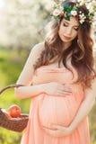 Eine schwangere Frau in einem Frühlingsgarten mit Korb Lizenzfreies Stockbild