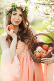 Eine schwangere Frau in einem Frühlingsgarten mit Korb Stockbild