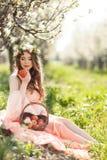 Eine schwangere Frau in einem Frühlingsgarten mit Korb Stockfotografie