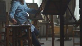 Eine schwangere Frau wird angespornt, ein Bild zu malen Ein Frauenmaler Stockbild