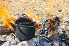 Eine schwarze geräucherte Teekanne steht auf dem Feuer, das durch gelbe Flammenzungen vor dem hintergrund des trockenen Grases -  Stockfotos
