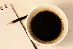 Eine schwarze heiße Spindel von Kaffeeständen nahe bei einem Notizblock mit einem Stift lizenzfreies stockfoto