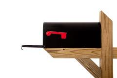 Eine schwarze Mailbox auf einem hölzernen Pfosten lizenzfreies stockbild