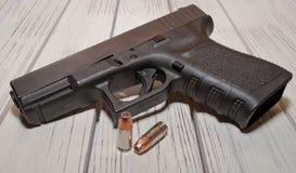 Eine schwarze Pistole mit Kugeln auf einem Holztisch Stockfotos