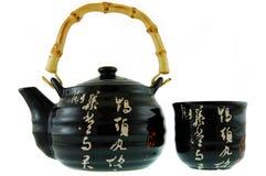 Eine schwarze Teekanne mit einem Cup Lizenzfreie Stockfotos