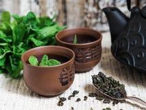 Eine schwarze Teekanne mit grünem Tee und eine Schale für Tee Lizenzfreie Stockfotos