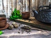 Eine schwarze Teekanne mit grünem Tee und eine Schale für Tee nahe bei einem Zweig der Minze Lizenzfreie Stockfotografie