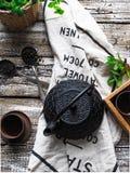 Eine schwarze Teekanne mit grünem Tee und eine Schale für Tee nahe bei einem Zweig der Minze Stockfoto