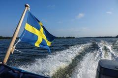 Eine schwedische Flagge auf der Rückseite eines Bootes stockbilder