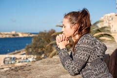 Eine sehnsüchtige Mädchenstellung und das Beten macht einen Wunsch nahe dem Geländer über dem Meerwasser an einem hellen sonnigen stockbild