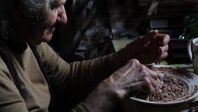 Eine sehr alte kranke Frau analysiert die Reste f?r das Kochen des Abendessens, Leben auf dem Bauernhof stock video
