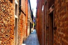 Eine sehr schmale Straße in Venedig mit Wänden des roten Backsteins und verwischt Lizenzfreies Stockfoto
