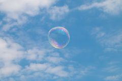 Eine Seifenblase, die durch den Himmel schwimmt Lizenzfreie Stockfotografie