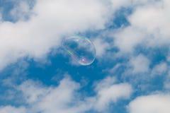 Eine Seifenblase, die durch den Himmel schwimmt Stockfotografie